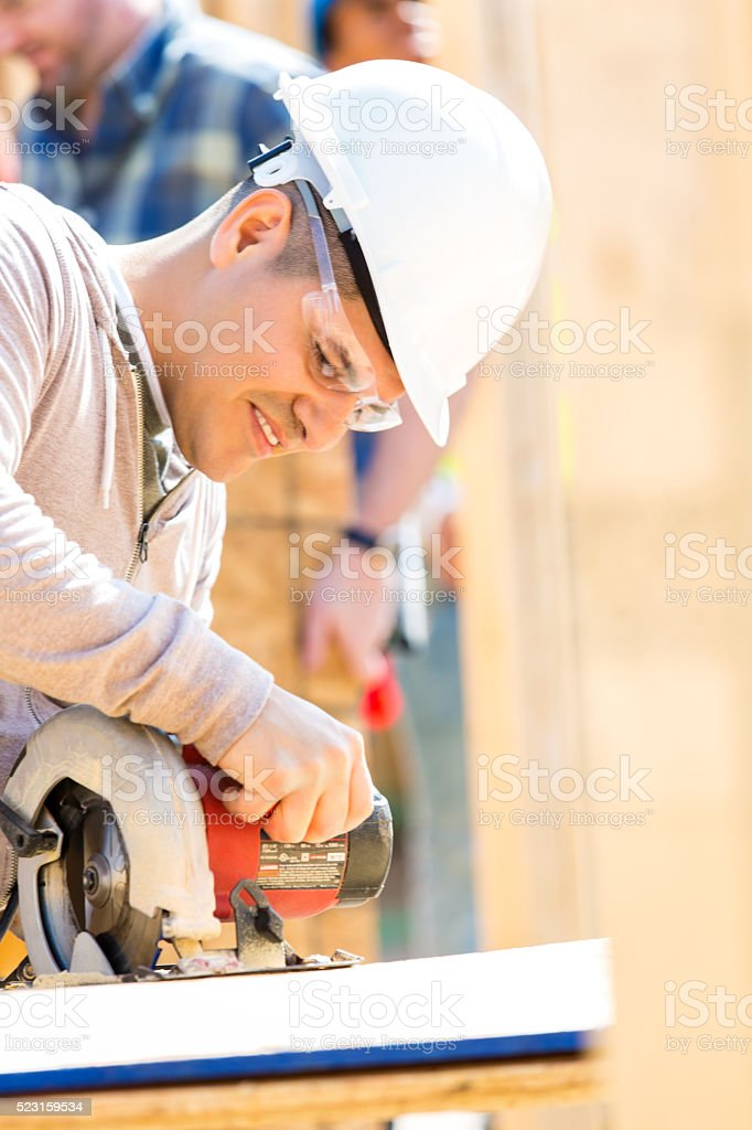Construction worker uses power tool at job site stock photo