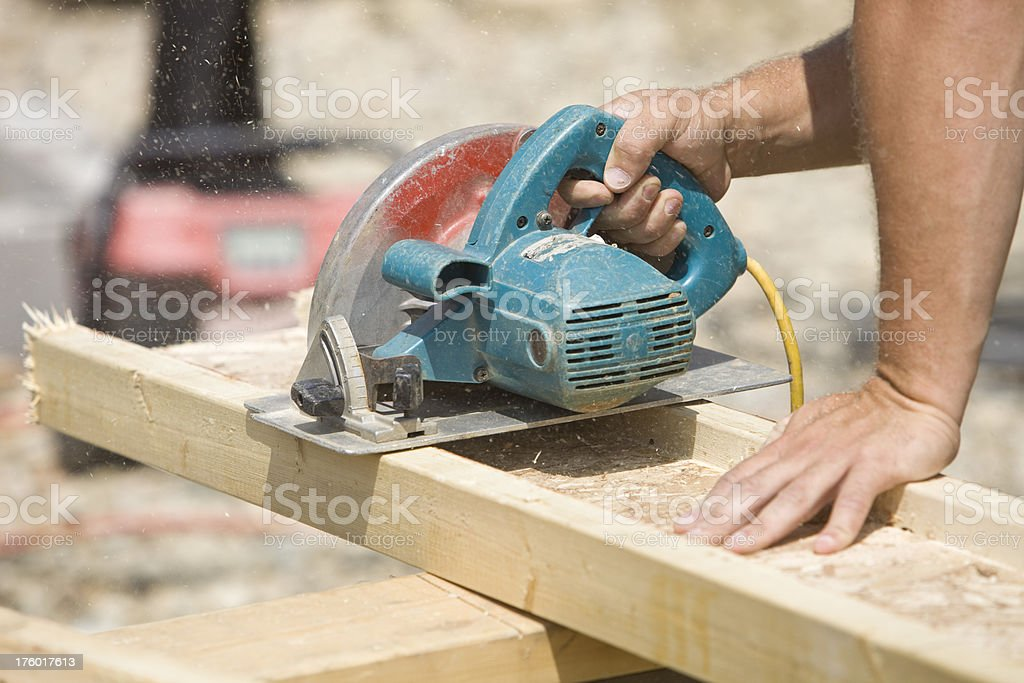 Construction Worker Using a Circular Saw on Job Site stock photo