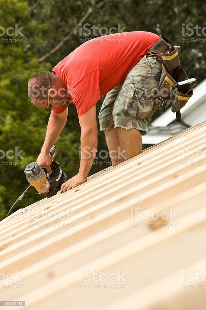 Construction Worker Using a Framing Nailer on Job Site stock photo