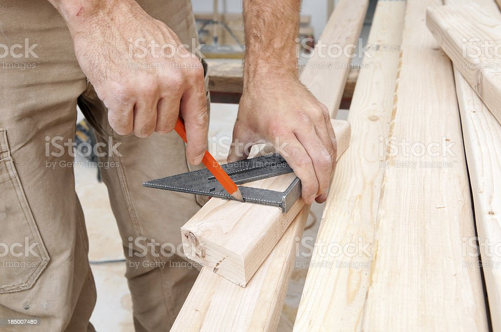 Construction Worker Using a Speed Square to Mark Stud stock photo