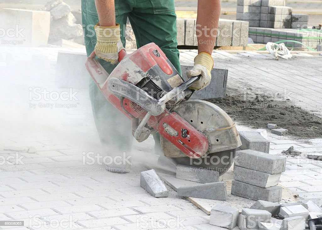 Construction worker using cement block cutter stock photo