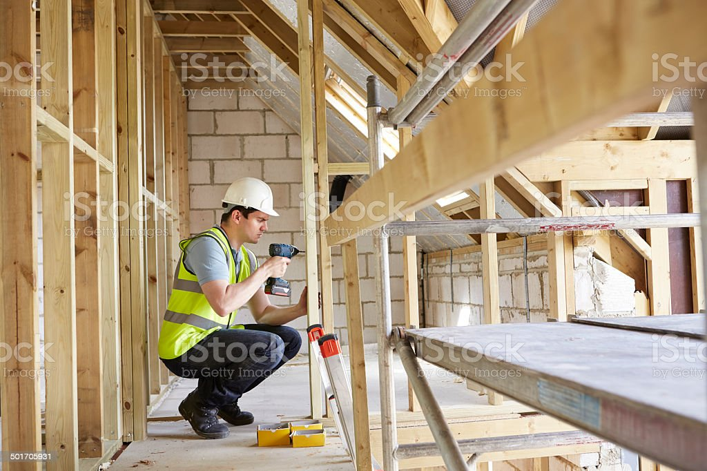 Construction Worker Using Drill On House Build stock photo