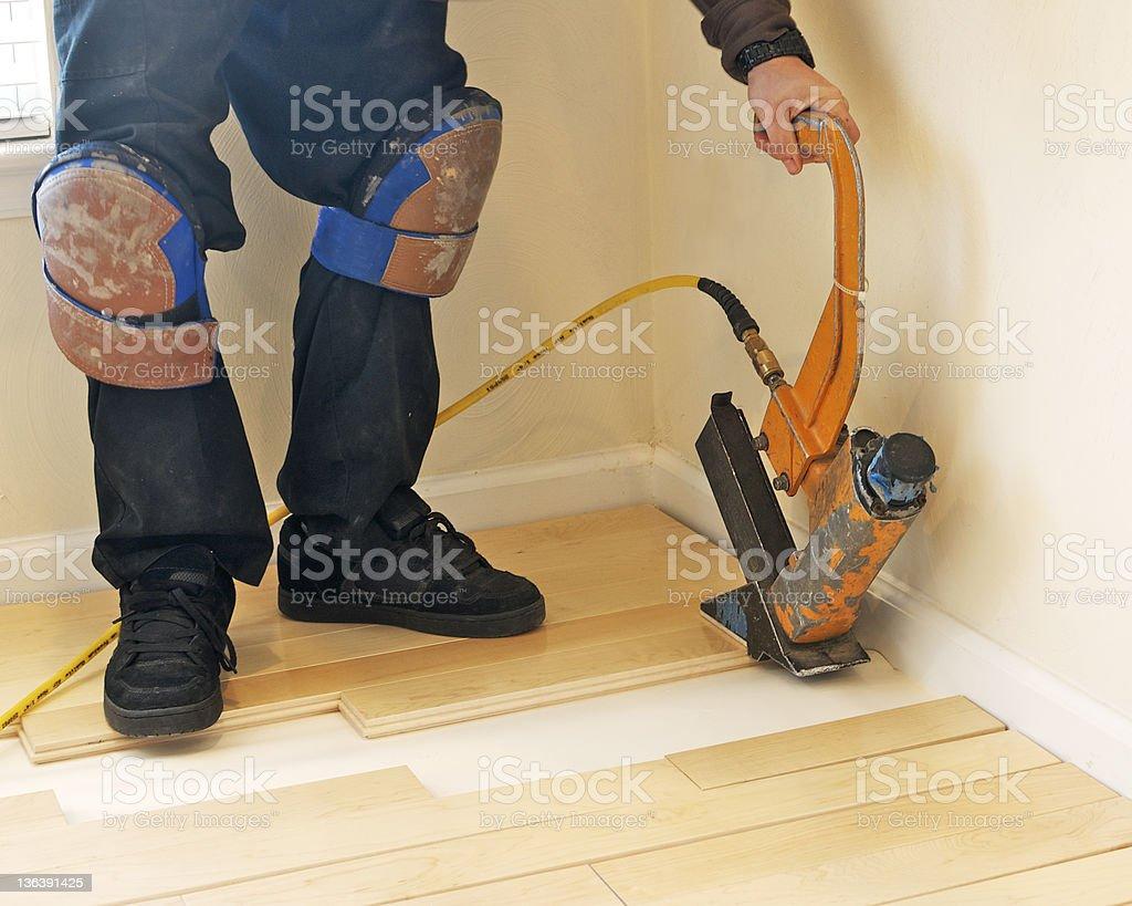 Construction worker using hardwood nail gun. stock photo