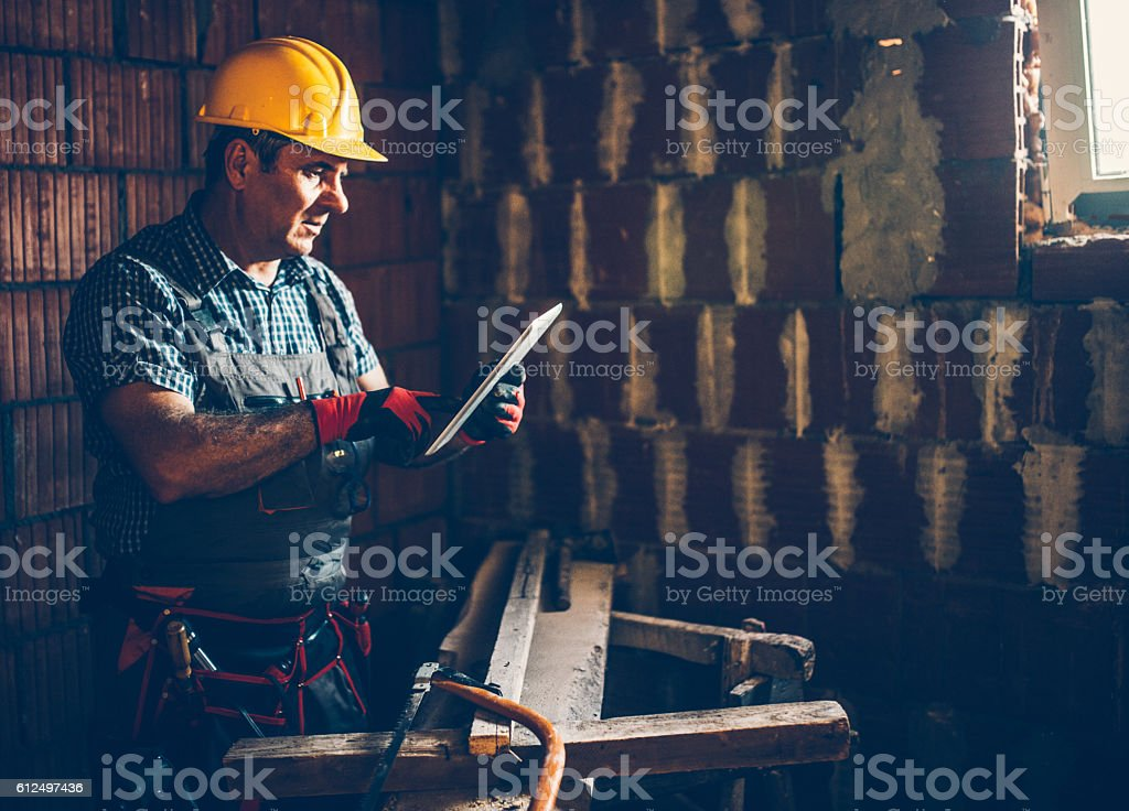 Construction worker using lap top stock photo