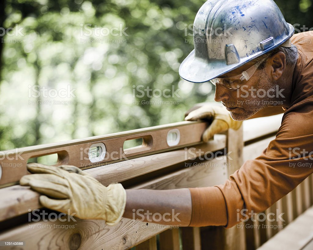 Construction Worker Using Level on Deck Rail stock photo