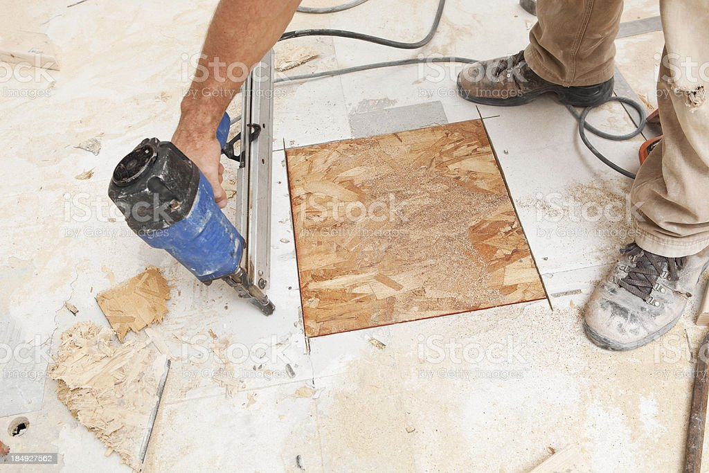 Construction Worker Using Nail Gun to Fasten Floor Patch stock photo
