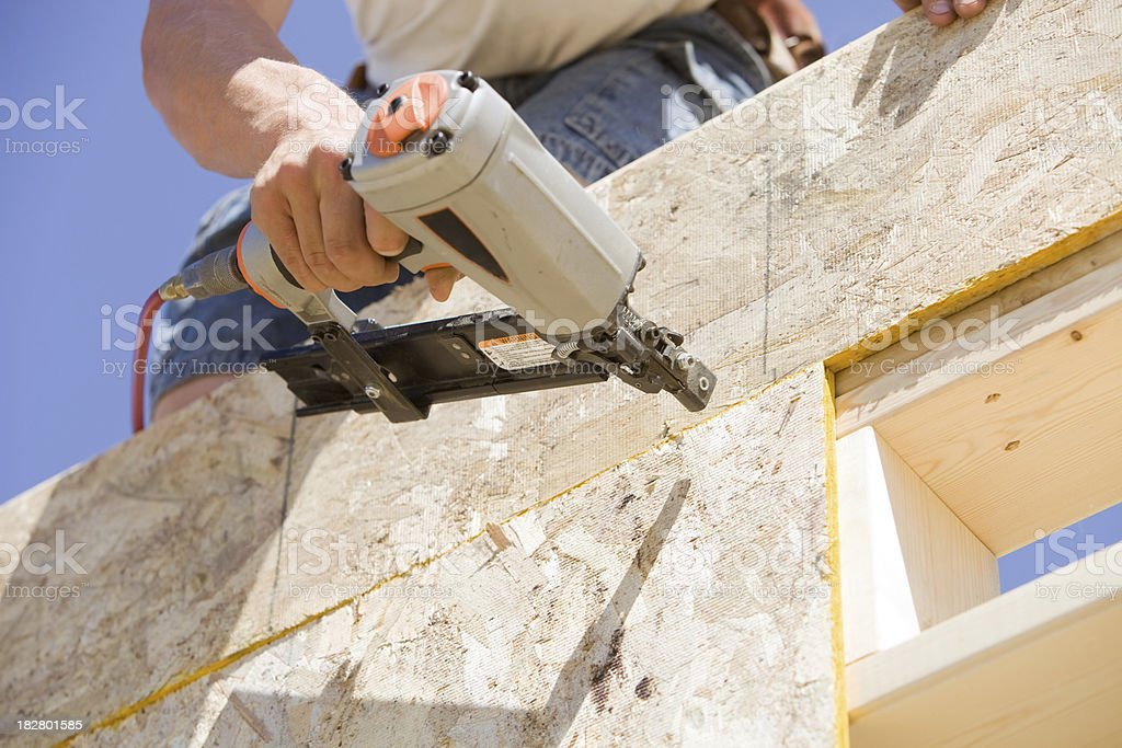 Construction Worker Using Pneumatic Stapler to attach OSB Sheathing stock photo