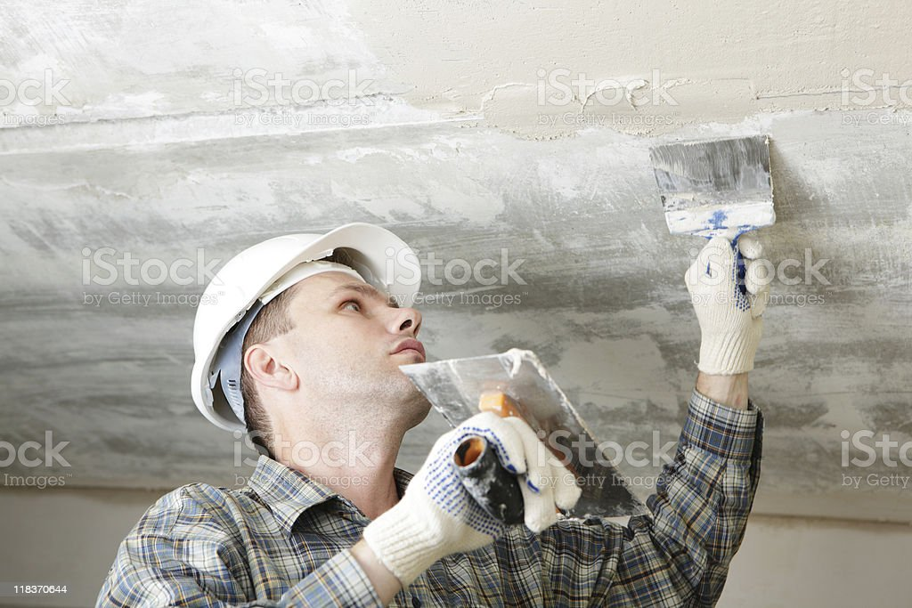 Construction worker wearing a hard hat plastering a ceiling royalty-free stock photo