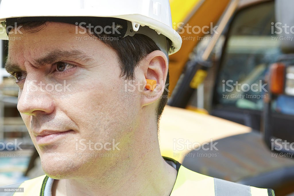 Construction Worker Wearing Protective Ear Plugs stock photo