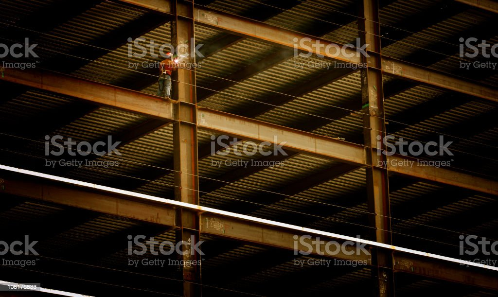 Construction Worker Welding Beam on High Rise Building stock photo