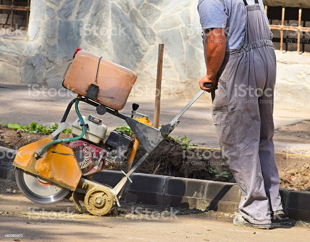 Construction worker with an asphalt sawing machinery stock photo