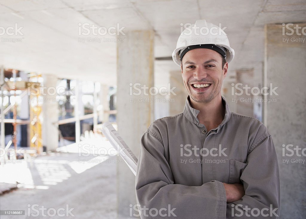 Construction worker with arms crossed on construction site stock photo