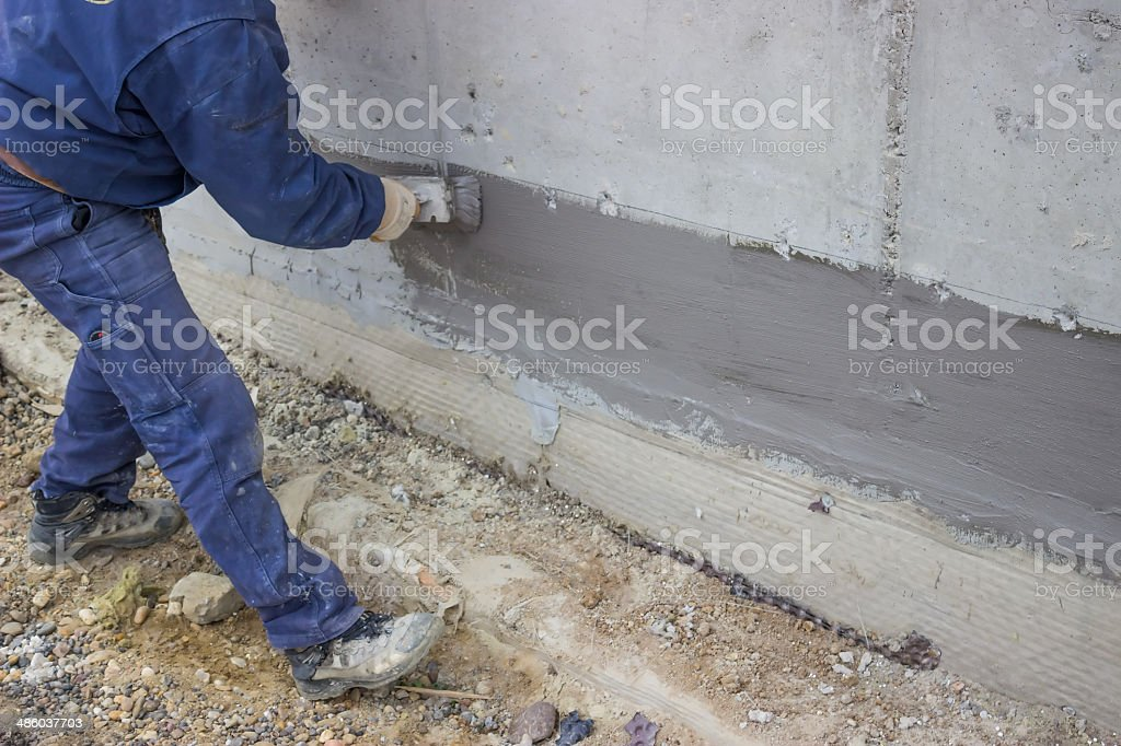 Construction worker with brush applied hydro insulation stock photo