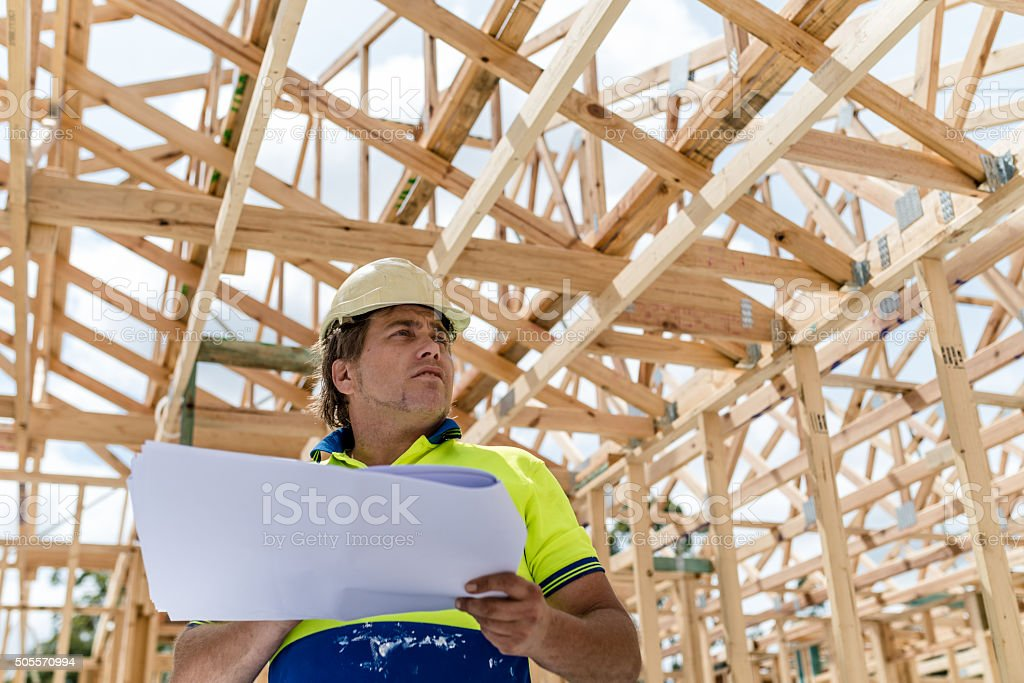 Construction worker with building plan stock photo