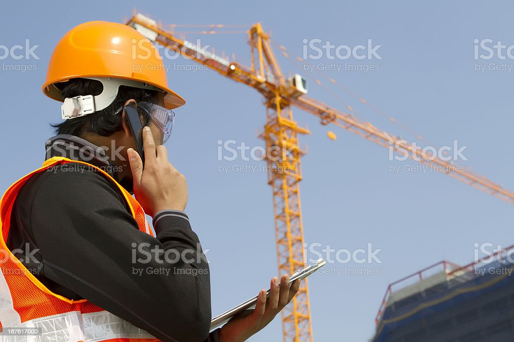 construction worker with crane in background royalty-free stock photo