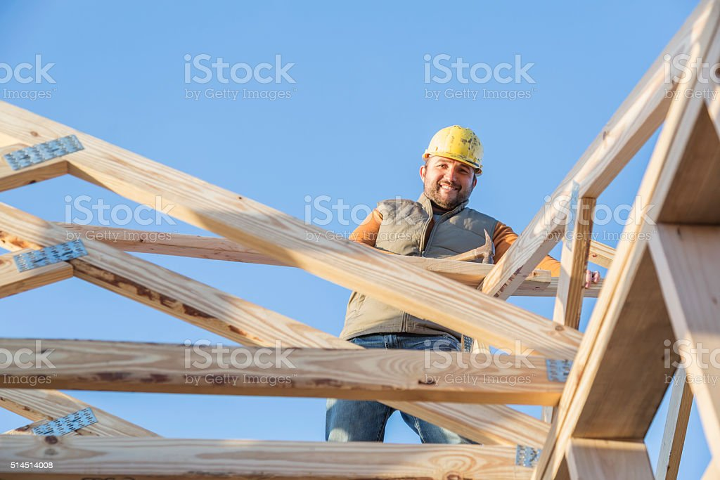 Construction worker with hammer on roof of house frame stock photo