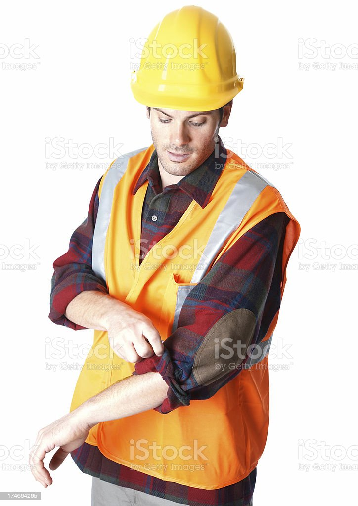 Construction worker with hard hat rolling up his sleeves royalty-free stock photo