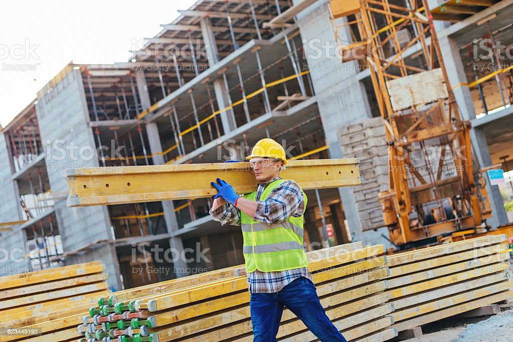 Construction worker with hardhat carrying planks stock photo