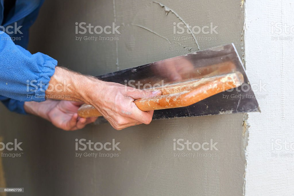Construction worker with long trowel plastering a wall stock photo