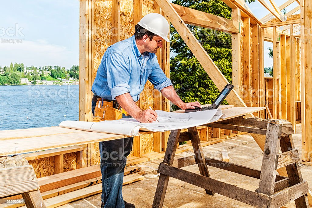 Construction Worker with Plans and Laptop stock photo
