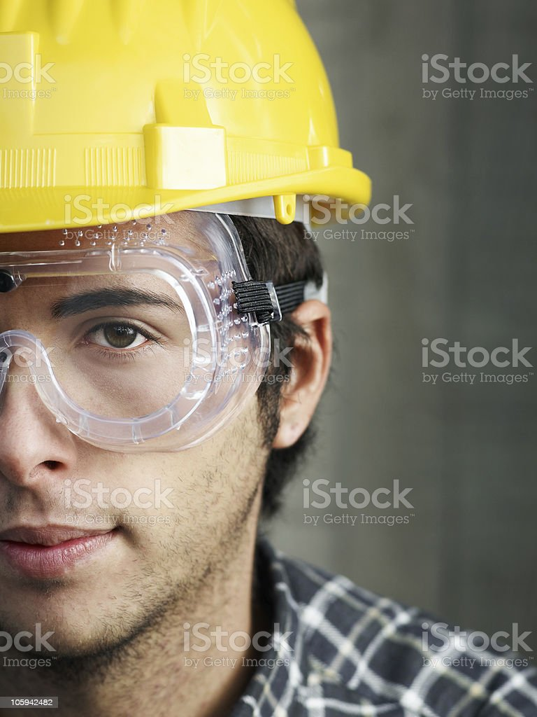 A construction worker with yellow safety hat and goggles stock photo