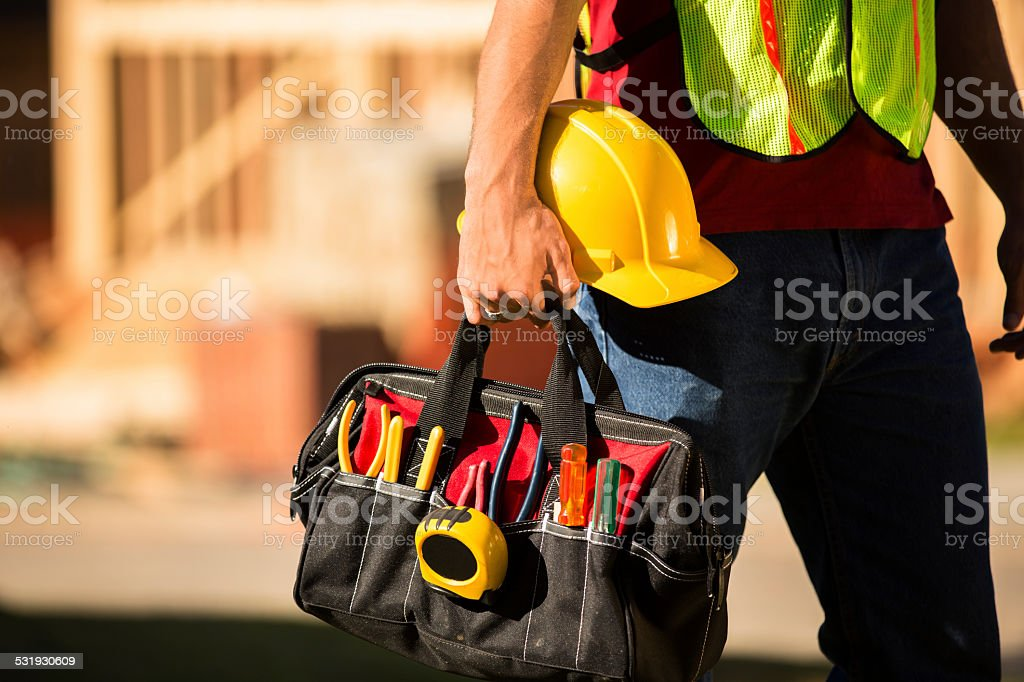 Construction worker working at a job site. Toolbag, hardhat. stock photo