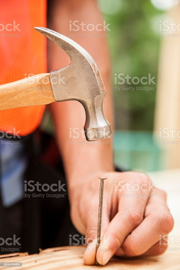 Construction worker working at job site, framed building. Hammer, nail. stock photo