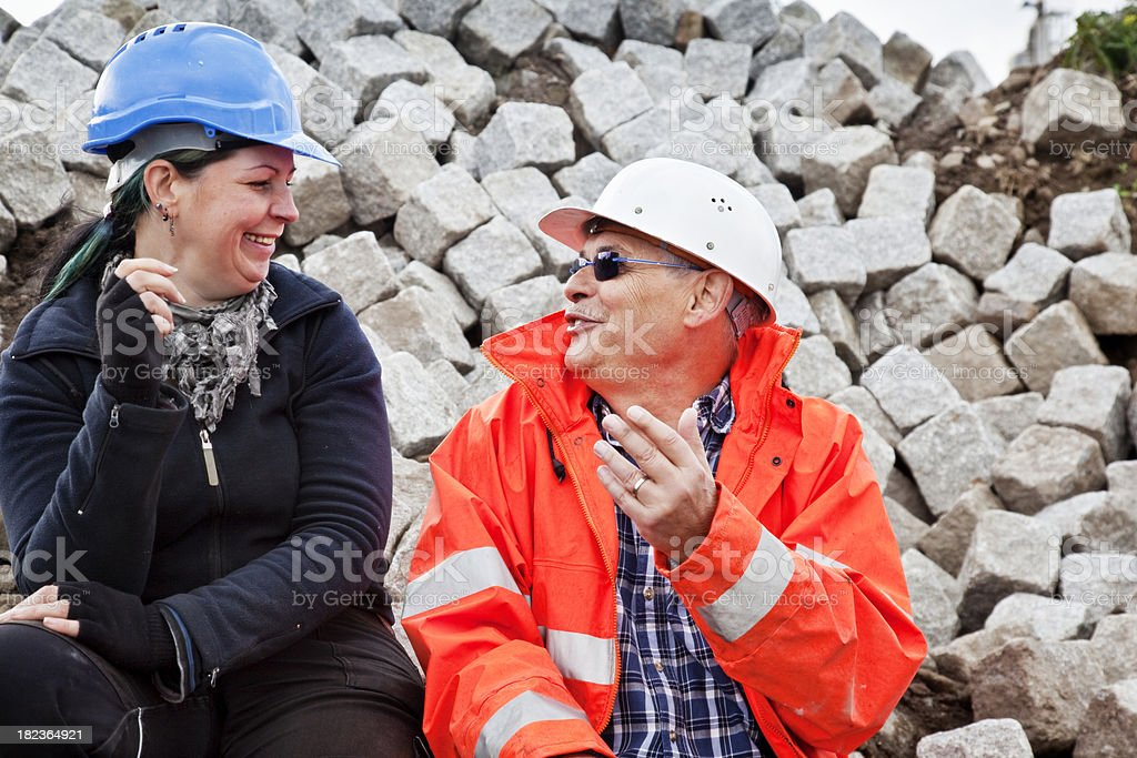 construction workers at a break talking and smiling royalty-free stock photo