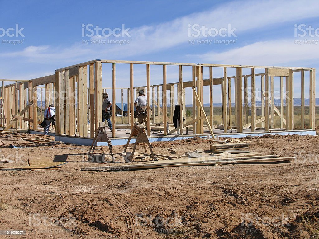 Construction workers at a building site with wood royalty-free stock photo