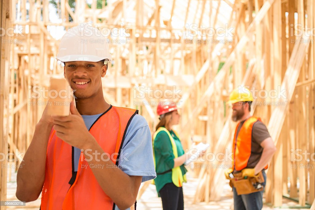Construction workers busy working at job site. stock photo