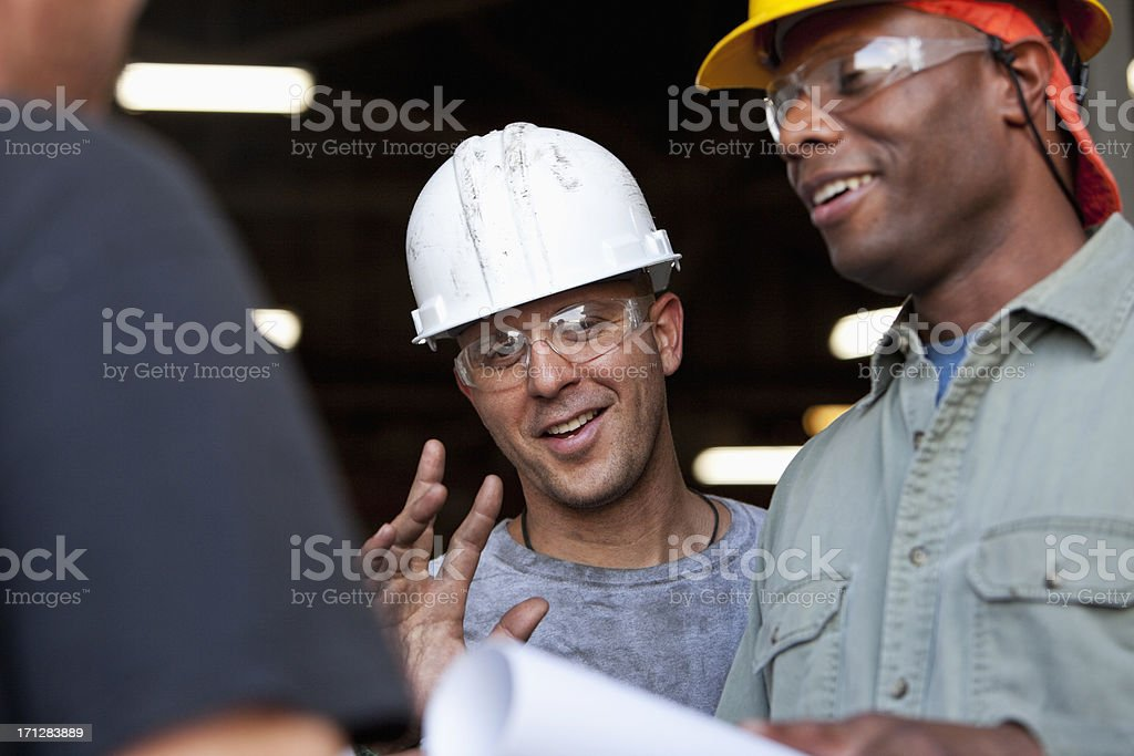 Construction workers chatting and looking at plans stock photo