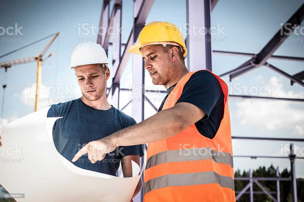 Construction Workers Checking Blueprints stock photo