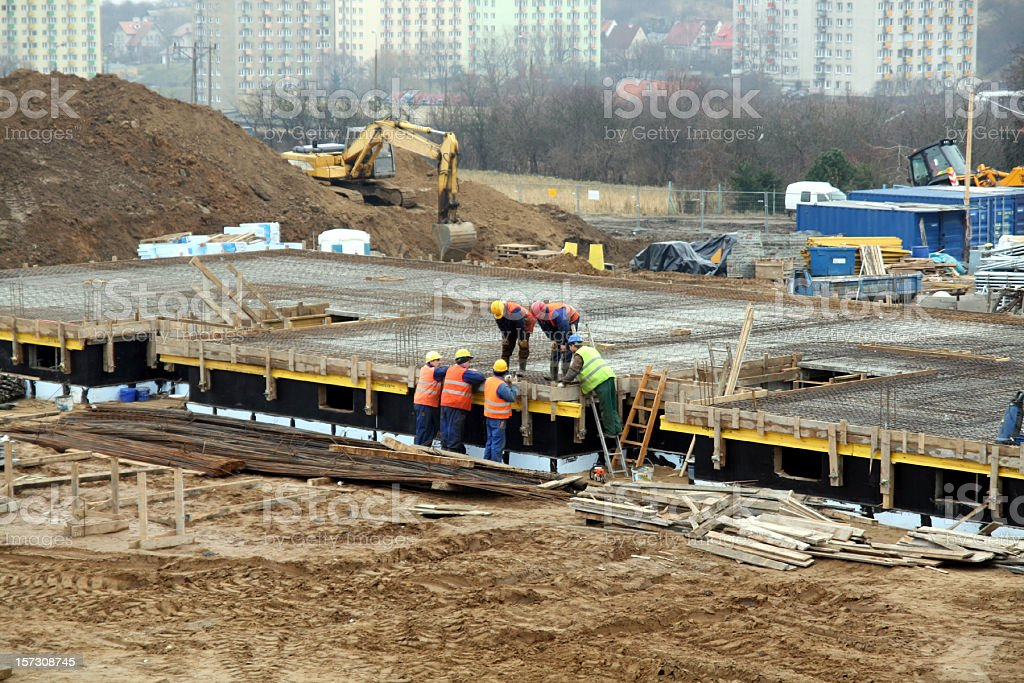 Construction workers consult building plans royalty-free stock photo