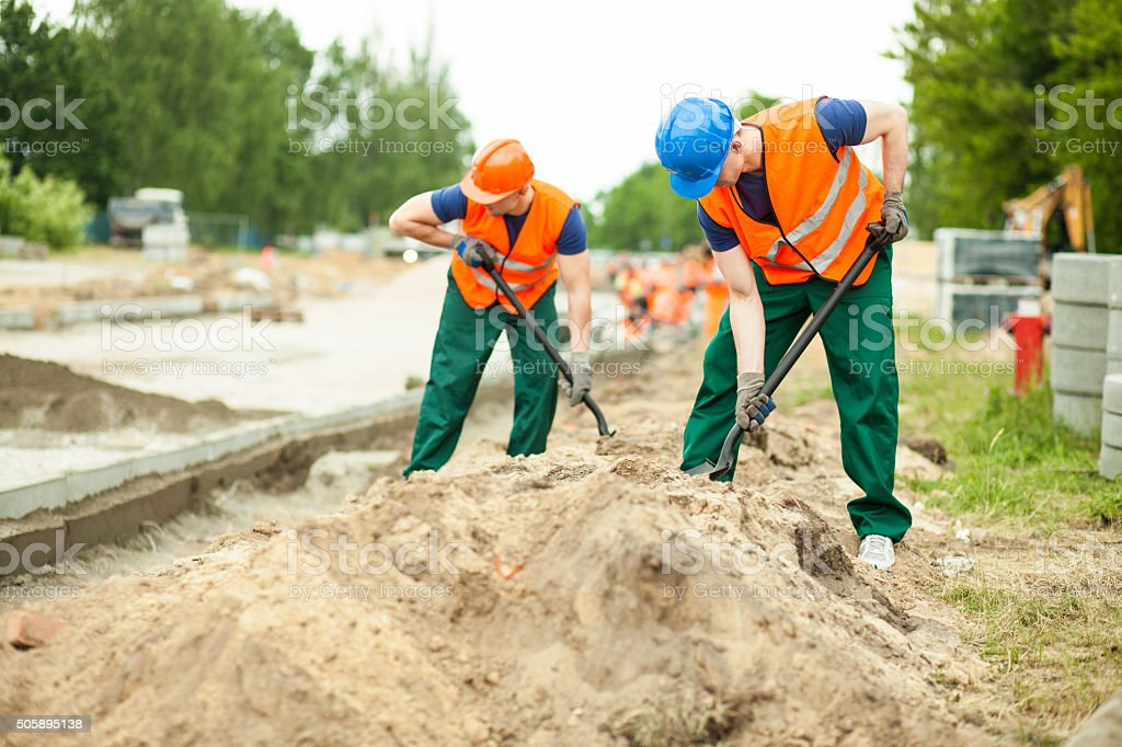 Construction workers digging stock photo