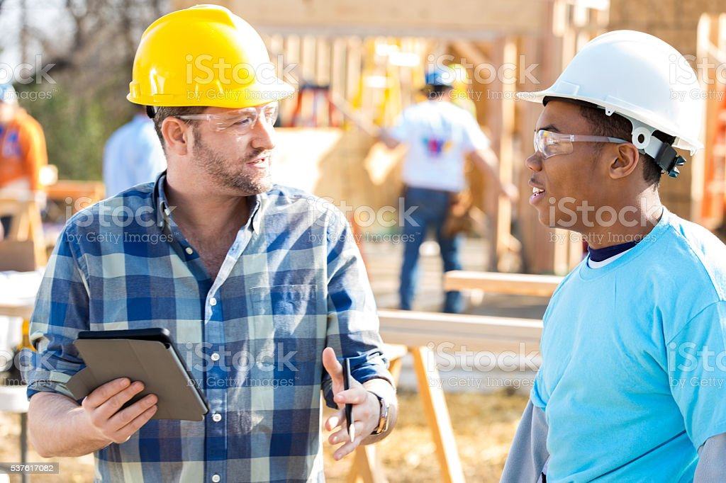 Construction workers discuss new home stock photo