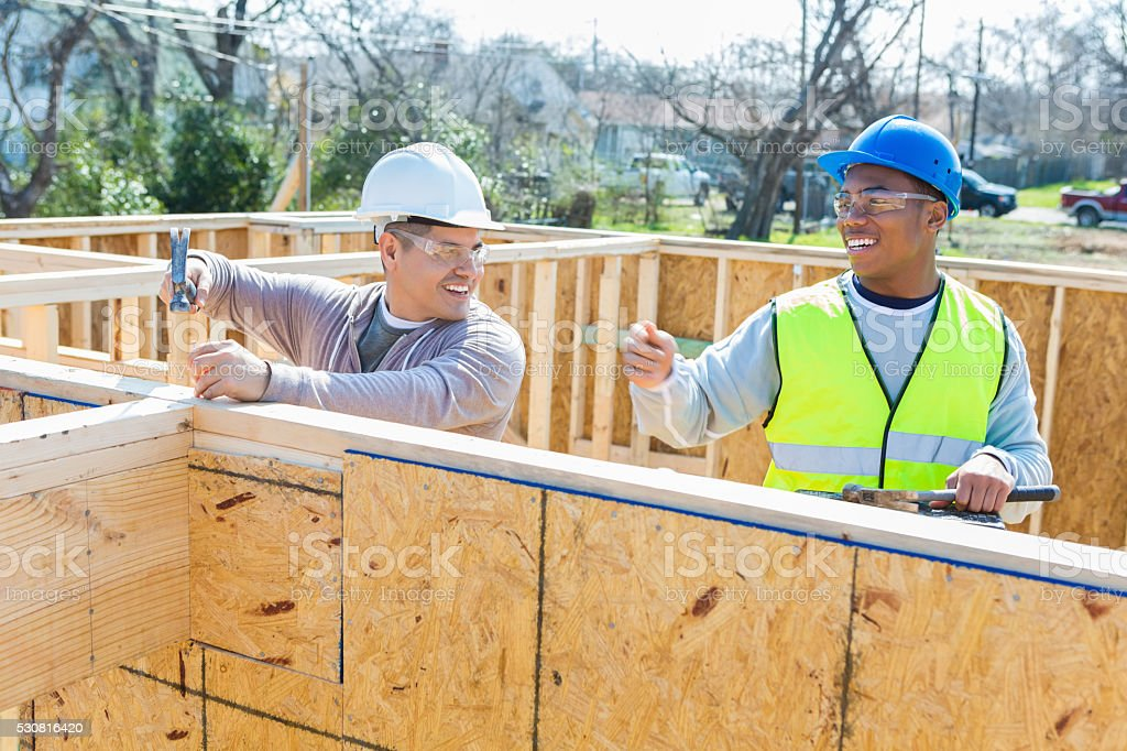 Construction workers discuss project while working stock photo