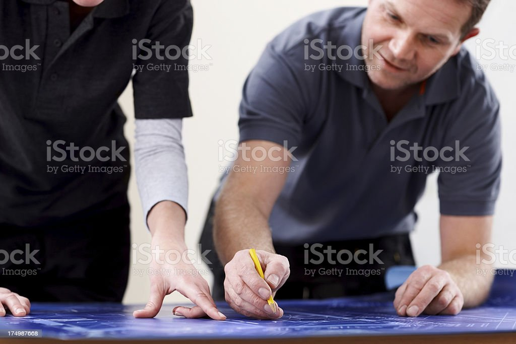 Construction workers discussing plans over drawings royalty-free stock photo
