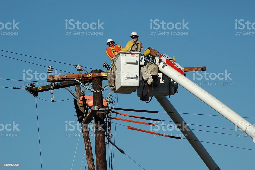 Construction workers fixing a telephone pole stock photo