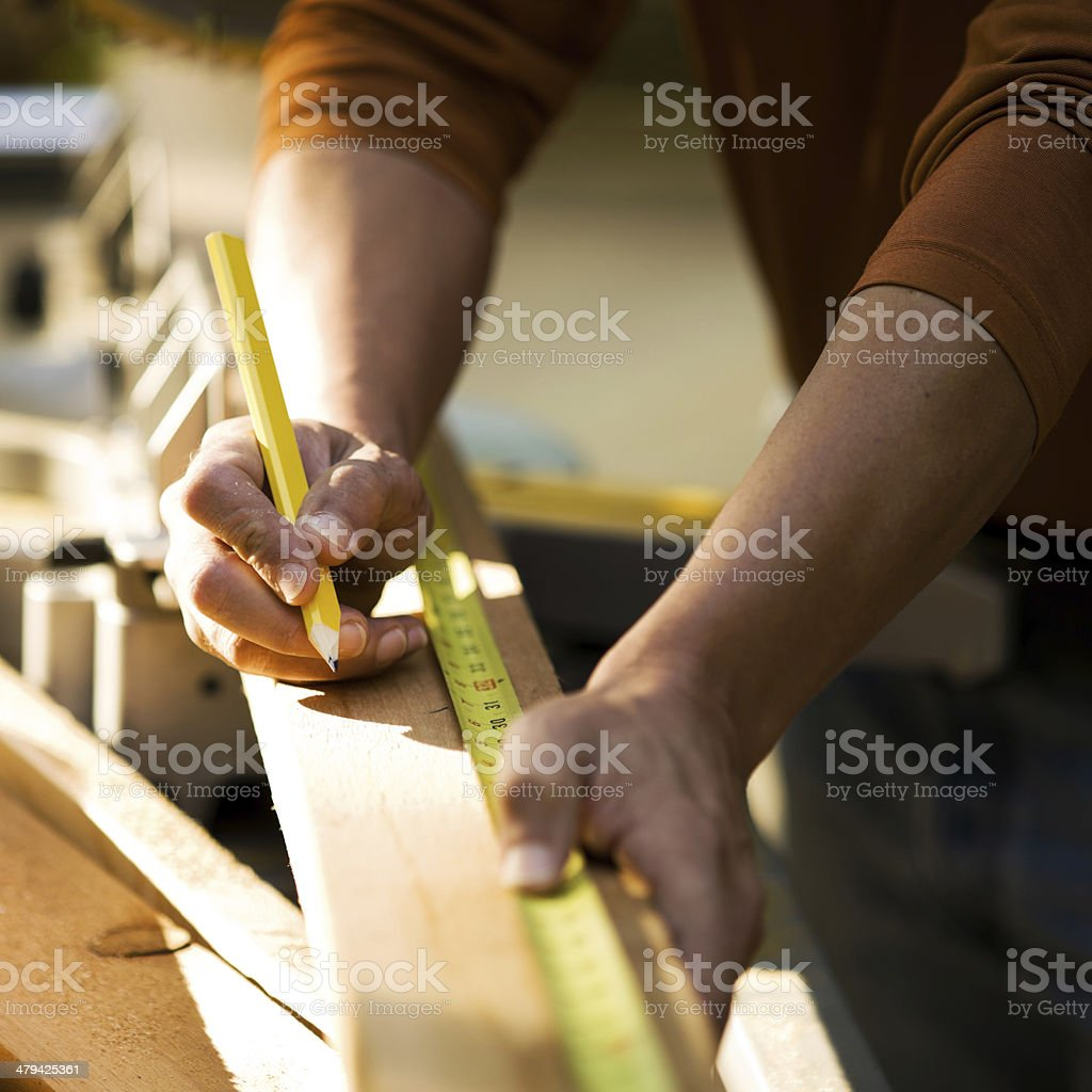 Construction Workers Hands Measuring Lumber stock photo