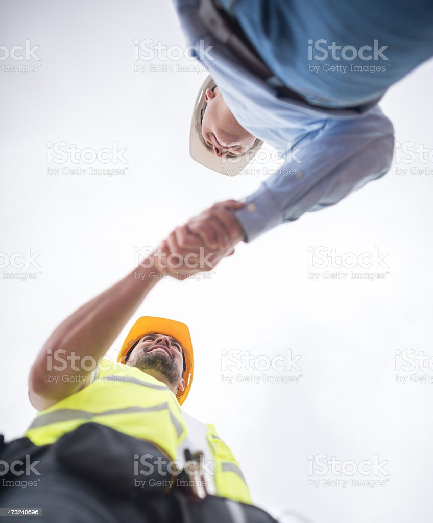 Construction workers handshaking stock photo