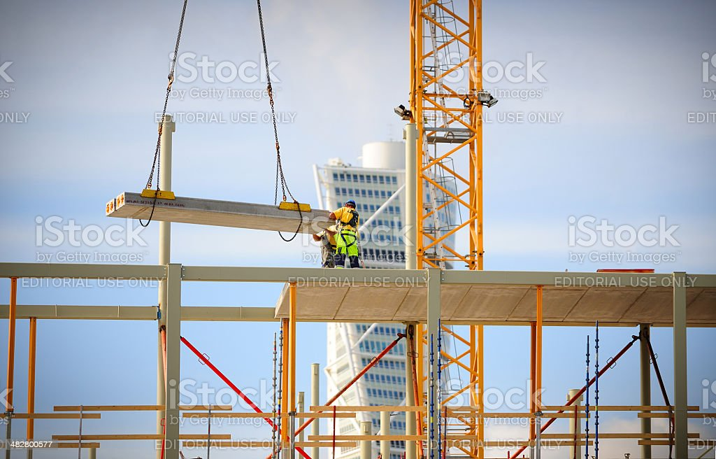Construction workers in profile working with a crane. royalty-free stock photo