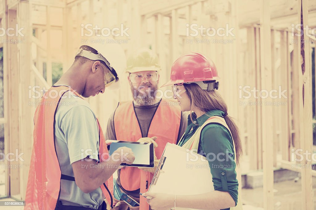 Construction workers busy working inside a job site. The multi-ethnic...