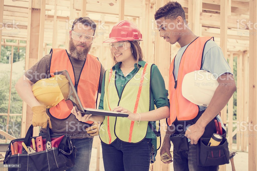Construction workers inside job site. Framed building. Laptop. stock photo