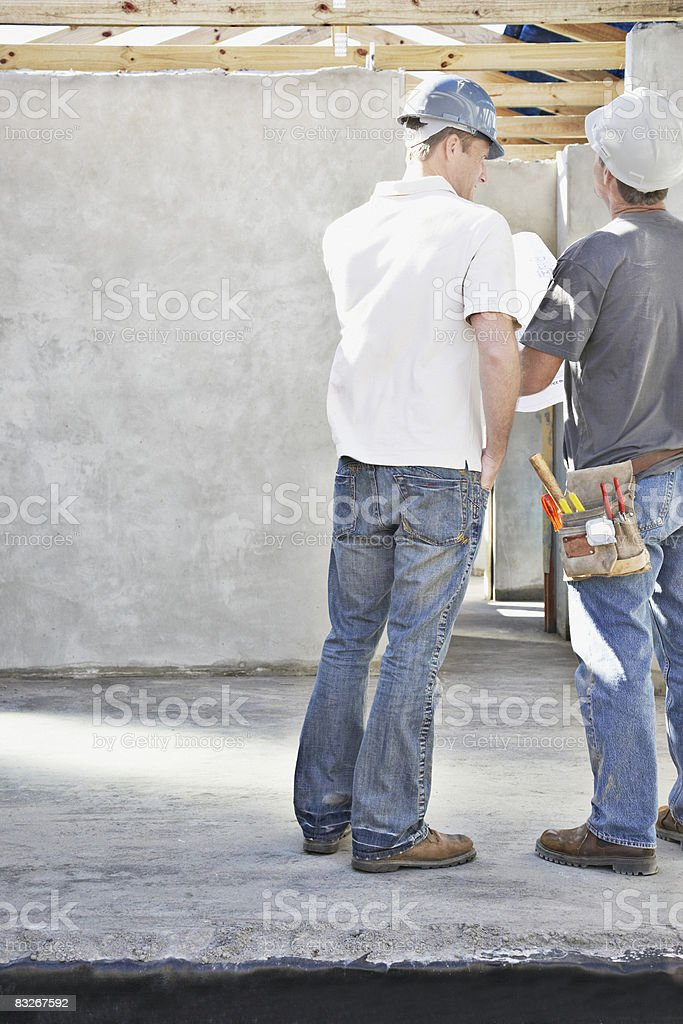 Construction workers inside unfinished new home royalty-free stock photo
