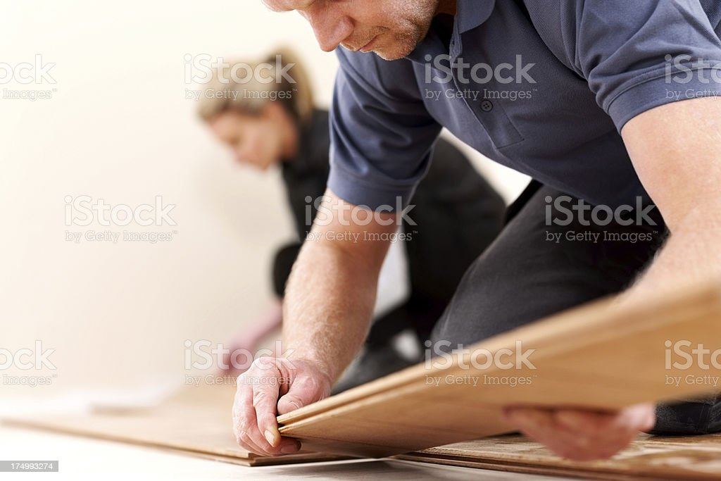Construction workers installing new wooden floor stock photo