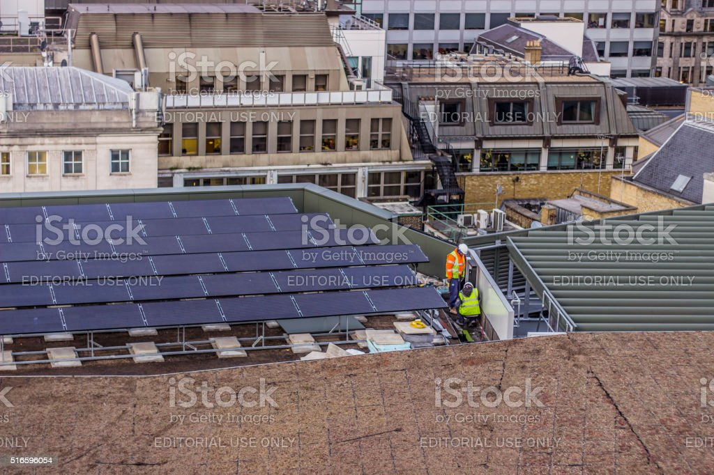 Construction workers installing solar panels stock photo