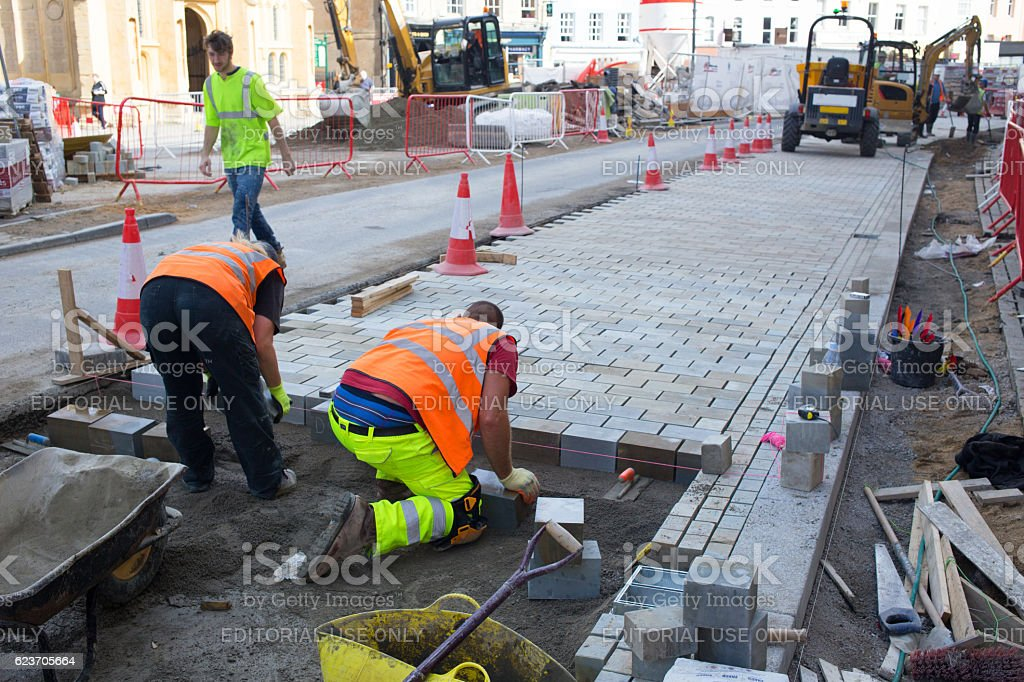 Construction workers laying slabs stock photo