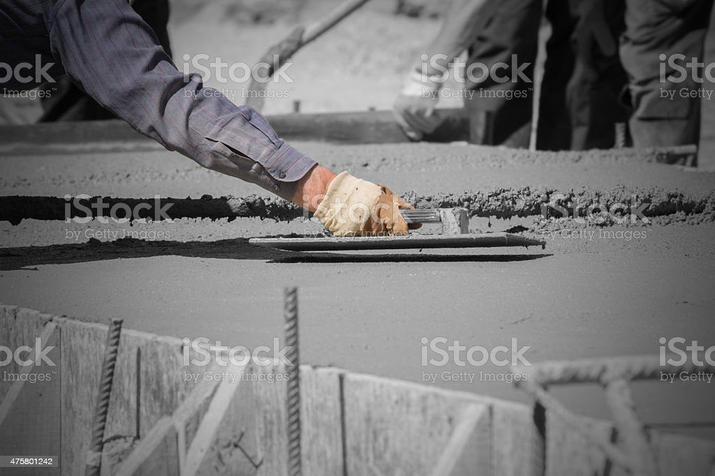 Construction workers leveling concrete pavement. stock photo