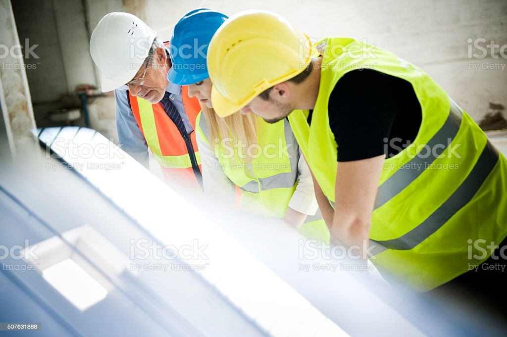 Construction workers looking at blueprint on construction site stock photo