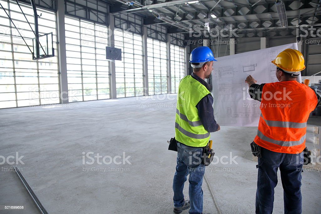Construction workers looking at blueprints inside construction site stock photo
